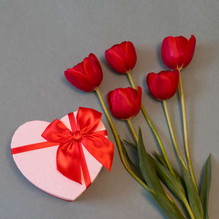 Red tulips and gift box in heart shape with red bow on pastel paper background. Beautiful spring floral layout. Greeting card for Valentines, womens or mothers day. Flat lay, top view, copy space Stock Photo