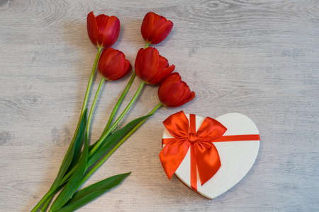 Red tulips and gift box in heart shape with red bow on light wooden background. Beautiful spring floral layout. Greeting card for Valentine's, women's or mother's day. Flat lay, top view, copy space