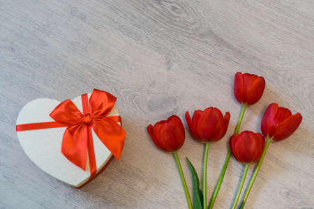 Red tulips and gift box in heart shape with red bow on light wooden background. Beautiful spring floral layout. Greeting card for Valentines, womens or mothers day. Flat lay, top view, copy space Stock Photo