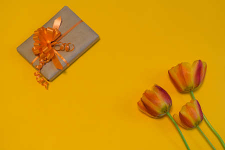 Orange tulips and gift box wrapped in kraft paper with orange bow on bright yellow background. Beautiful spring layout. Greeting card for womens or mothers day. Flat lay, top view, copy space