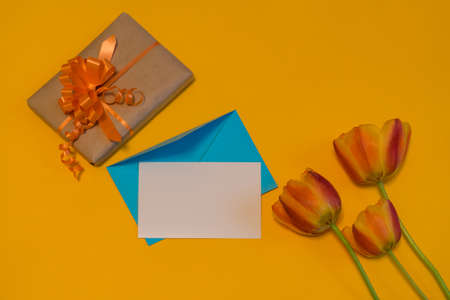 Orange tulips, gift box, empty card and evenlope on bright yellow background. Beautiful spring mock up. Greeting card for womens or mothers day. Flat lay, top view, copy space