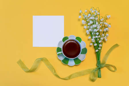 Bouquet of lilies of the valley flowers with green ribbon, tea cup and empty card on bright yellow paper background. Beautiful spring mock up, good morning concept. Top view, flat lay, copy space