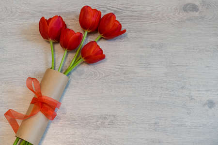 Red tulips in kraft paper with red bow on light wooden background. Beautiful spring floral layout. Greeting card for womens or mothers day. Flat lay, top view, copy space