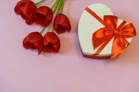 Red tulips and gift box in heart shape with red bow on pink pastel background. Beautiful spring floral layout. Greeting card for Valentines, womens or mothers day. Flat lay, top view, copy space