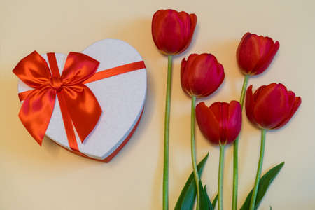 Red tulips and gift box in heart shape with red bow on light pastel background. Beautiful spring floral layout. Greeting card for Valentines, womens or mothers day. Flat lay, top view
