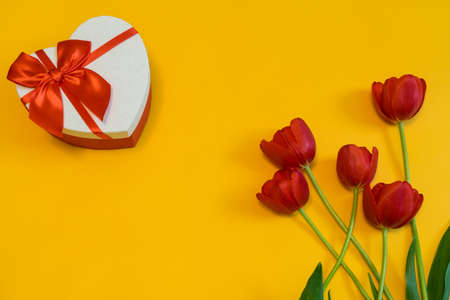Red tulips and gift box in heart shape with red bow on yellow background. Beautiful spring floral layout. Greeting card for Valentines, womens or mothers day. Flat lay, top view, copy space