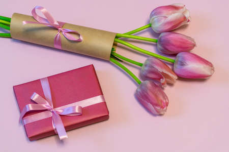 Bouquet of beautiful pink fresh tulips and gift box on pastel paper background. Greeting card for valentines, womens or mothers day. Flat lay, top view