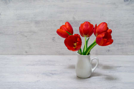 Bouquet of beautiful fresh red tulips in small white jug on light wooden background. Valentines, womens or mothers day concept. Greeting card for spring holiday. Still life, selective focus