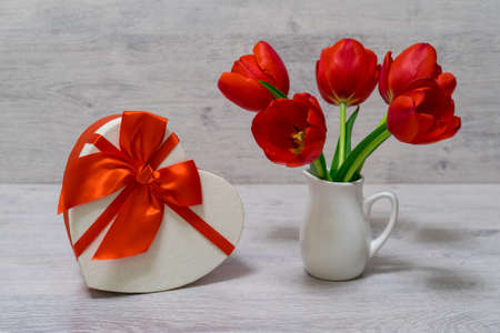 Bouquet of beautiful fresh red tulips in small white jug and gift box in heart shape on light background. Valentines, womens or mothers day concept. Greeting card, still life, selective focus