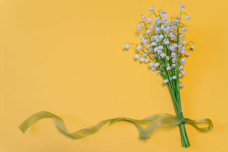 Bouquet of lilies of the valley flowers with green ribbon on bright yellow paper background. Beautiful spring composition in minimal style. Top view, flat lay, copy space