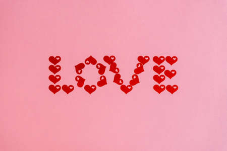 Text LOVE made of red confetti hearts on pink background. Love, romance or Valentines day concept