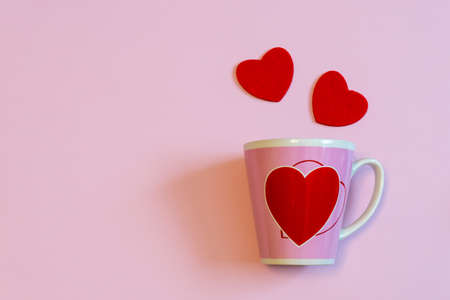 Mug for coffee or tea and two red hearts on pink pastel background. Creative layout in minimal style. Love, romance or Valentines day concept