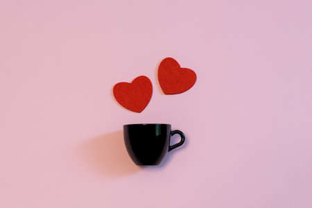 Black cup for coffee or tea and two red hearts on pink pastel background. Creative layout in minimal style. Love, romance or Valentines day concept