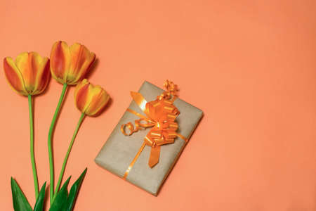 Orange tulips and gift box wrapped in kraft paper with orange bow on bright peachy background. Beautiful spring layout. Greeting card for womens or mothers day. Flat lay, top view, copy space