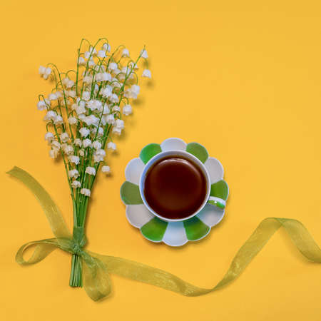 Bouquet of lilies of the valley flowers with green ribbon and tea cup on bright yellow background. Good morning concept. Beautiful spring composition in minimal style. Top view, flat lay, copy space