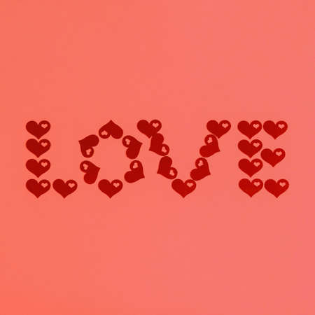 Text LOVE made of red confetti hearts on living coral background. Love, romance or Valentines day concept. Color of the year 2019 Stock Photo