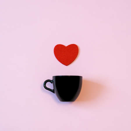 Black cup for coffee or tea and red heart on pink pastel background. Creative layout in minimal style. Love, romance or Valentines day concept Stock Photo