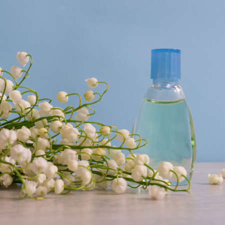 Small bottle of perfume and bouquet of lily of the valley flowers on light color background. Perfumery, fragrance, cosmetic concept. Spring or summer still life