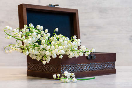 Bouquet of fresh lily of the valley flowers in small casket on light wooden background. Beautiful spring still life, copy space