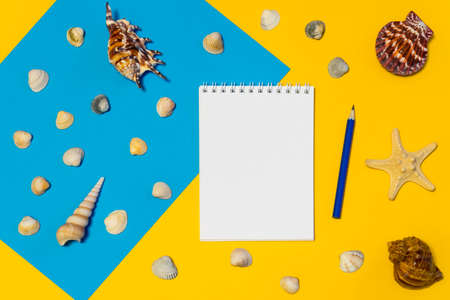Notebook and pencil with seashells and starfish on blue and yellow paper background. Mock up, flat lay, copy space, top view. Summer vacation concept 스톡 콘텐츠
