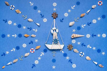 Symbole solaire composé d'objets de décoration et de jouets miniatures : coquillages, étoiles de mer, ancres, volants, bouées de sauvetage, phares. Composition créative avec bateau. Concept de vacances d'été et de voyage en mer Banque d'images