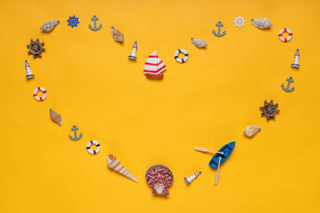 Heart symbol made of decorative items and miniature toys: seashells, boat, vessel, anchors, steering wheels, life buoys. Creative composition, copy space. Summer vacation, sea travel concept.