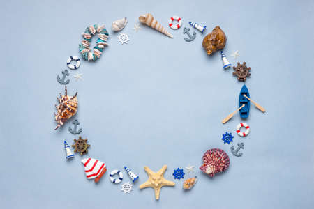 Round frame made of decorative items and miniature toys: seashells, seastars, vessel, boat, anchors, steering wheels, life buoys. Creative composition, mock up. Summer vacation and sea travel concept Banco de Imagens