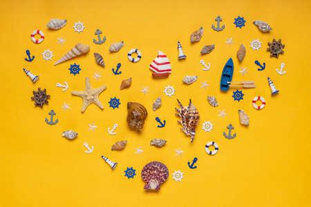 Heart symbol made of decorative items and miniature toys: seashells, seastar, boat, vessel, anchors, steering wheels, life buoys. Creative composition, flat lay. Summer vacation, sea travel concept