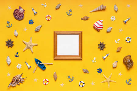 Round frame made of decorative items and miniature toys: seashells, seastars, vessel, boat, anchors, steering wheels, life buoys. Empty wooden photoframe, mock up. Summer vacation, sea travel concept Banco de Imagens