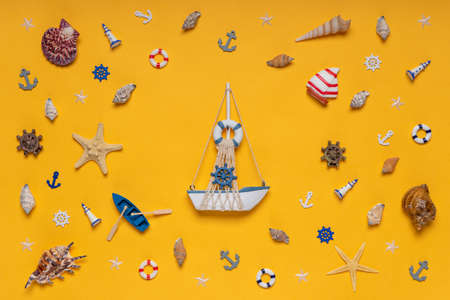 Round frame made of decorative items and miniature toys: seashells, seastars, vessel, boat, anchors, steering wheels, life buoys. Creative composition with ship. Summer vacation and sea travel concept Banco de Imagens