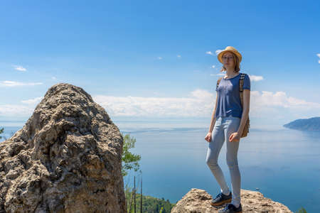 Cute tween tourist girl in hat and backpack standing on cliff top and posing against beautiful landscape of blue sky and Baikal lake. Hiking, travelling and summer vacation concept.
