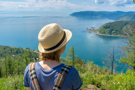 Tween tourist girl in hat and backpack standing on cliff top and admiring beautiful landscape of Baikal lake and Angara river source. Hiking, travelling and summer vacation concept.