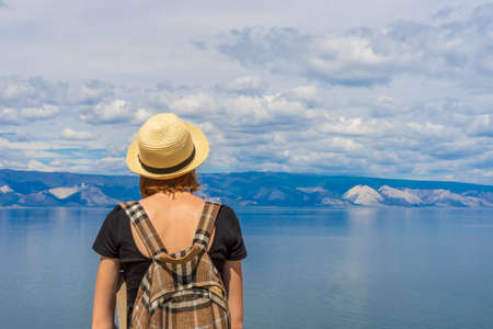 Attractive tween tourist girl in hat and backpack standing on cliff top and admiring beautiful landscape of blue sky and Baikal lake. Hiking, travelling and summer vacation concept.