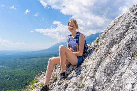 Tween tourist girl sitting on mountain cliff and looking at camera againt blue sky and summer landscape of valley. Hiking, travelling and wanderlust concept. Eastern Sayan, Buryatia, Russia. Banco de Imagens