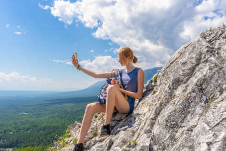 Tween tourist girl with smartphone take selfie sitting on mountain cliff againt blue sky and summer landscape of valley. Hiking, travelling and wanderlust concept. Eastern Sayan, Buryatia, Russia.