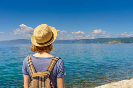 Tween tourist girl in hat and backpack admiring beautiful landscape of lake Baikal from waterfront of Listvyanka village in sunny summer day. Travelling, freedom and summer vacation concept.