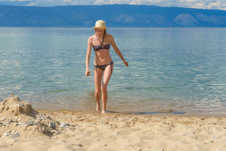 Cute tween girl in hat and bikini getting out of water after swimming in lake Baikal in summer sunny day. Beautiful young lady relaxing at beach. Summer vacation, outdoor recreation concept.