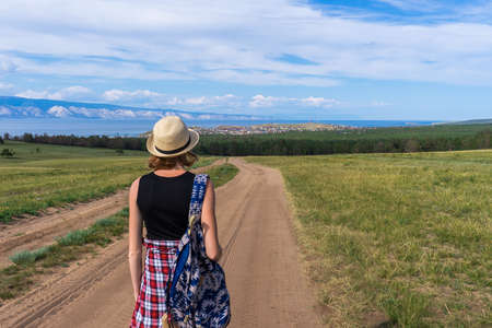 Tween tourist girl in hat and backpack walking on country road alone and admiring picturesque landscape of lake Baikal, mountains, village and blue sky. Travelling, hiking and summer vacation concept. Banco de Imagens