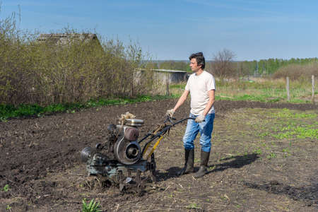 Man with cultivator ploughs ground. Land cultivation, soil tillage. Spring work in the garden. Gardening concept. Banco de Imagens