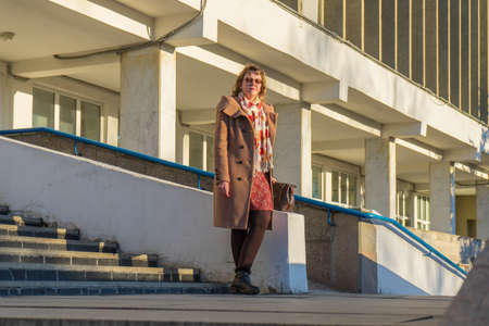 Attractive middle-aged woman wearing stylish coat standing with bag on stairs steps of office building in early spring at sunset. Street city portrait, fashion urban outfit.