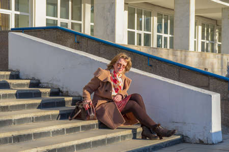 Attractive middle-aged woman wearing stylish coat and shoes sitting with bag on stairs step of office building in early spring at sunset. Street city portrait, fashion urban outfit. Banco de Imagens