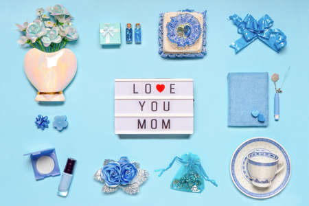 Stylish feminine accessories, flowers, cosmetics, gifts and decorative items in blue pastel colors on blue background. Text LOVE YOU MOM on lightbox, greeting card for mothers day. Flat lay.