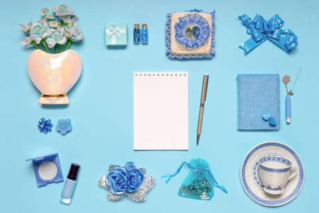 Stylish feminine accessories, flowers, cosmetics, gifts and decorative items in blue pastel colors on blue background. Empty notebook page, mock up. Womens or mothers day concept. Flat lay.