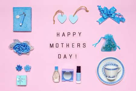 Stylish feminine accessories, flowers, cosmetics, perfume, gifts in blue pastel colors on pink background. Text HAPPY MOTHERS DAY, greeting card. Flat lay.