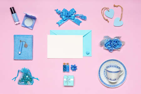 Stylish feminine accessories, flowers, cosmetics, gifts and decorative items in blue pastel colors on pink background. Empty white card for text, mock up. Womens or mothers day concept. Flat lay. Banco de Imagens