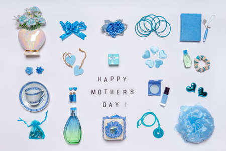 Stylish feminine accessories, flowers, cosmetics, jewelery, perfume in blue pastel colors on white background. Text HAPPY MOTHERS DAY on ligthbox, greeting card. Flat lay