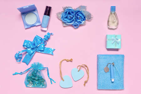 Frame made of stylish feminine accessories, flowers, cosmetics, gifts and decorative items in blue pastel colors on pink background. Space for text, mock up. Womens or mothers day concept. Flat lay.