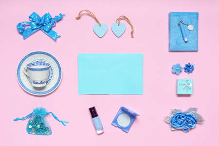 Stylish feminine accessories, flowers, cosmetics, gifts and decorative items in blue pastel colors on pink background. Empty blue card for text, mock up. Womens or mothers day concept. Flat lay.