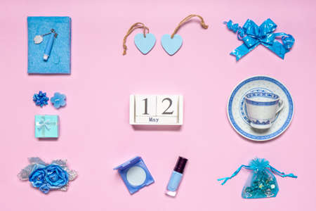 Stylish feminine accessories, flowers, cosmetics, gifts and decorative items in blue pastel colors on pink background. Calendar date May 12. Greeting card for mothers day in 2019. Flat lay, top view.