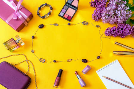 Fashion female accessories, flowers, cosmetics, perfume and jewelry on bright yellow background. Feminine concept, greeting card for womens or mothers day. Flat lay, top view, copy space.